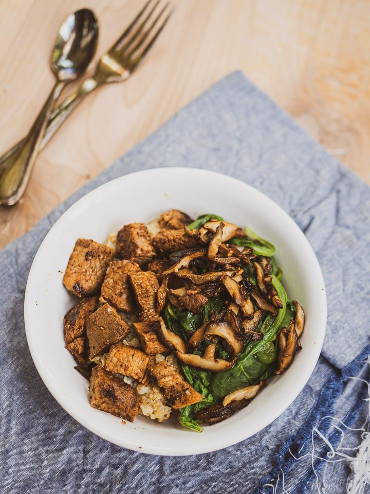 Sliced mushroom with steak cubes and spinach on top of savory oatmeal for inspiration for the savory oatmeal recipe