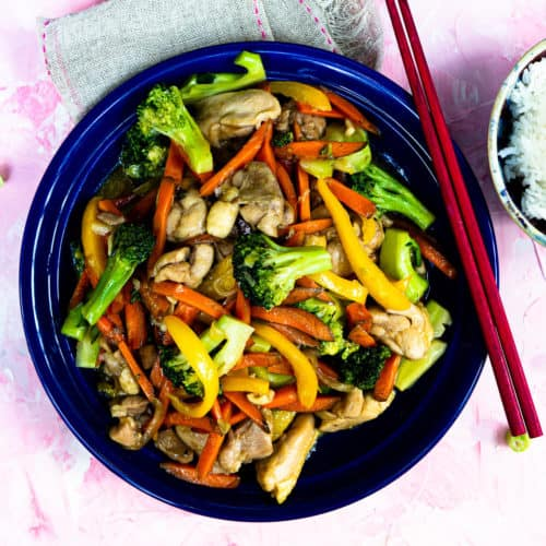 Chicken and broccoli stir fry on a blue plate with chopsticks