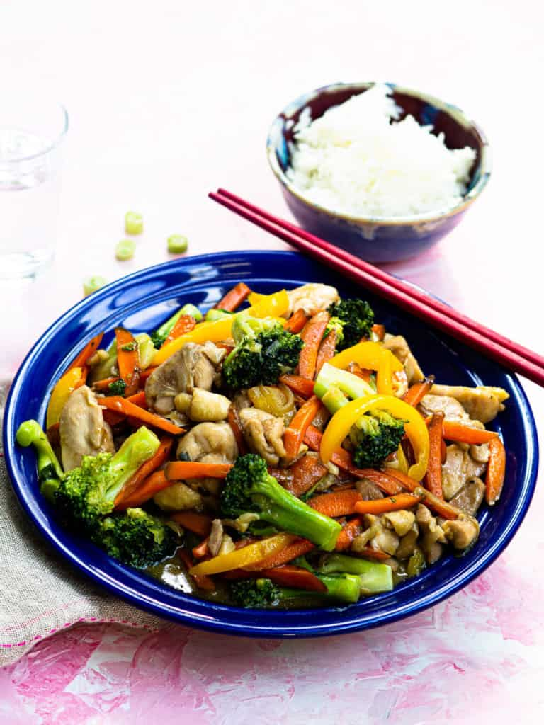 Chicken and broccoli stir fry on a blue plate with chopsticks and a bowl of rice