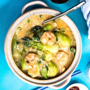 Overhead view of shrimp with lobster sauce and bok choy in a ceramic pot with a spoon