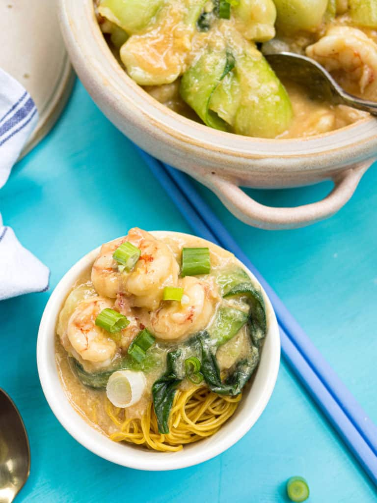 A bowl of wonton noodles topped with shrimp with lobster sauce