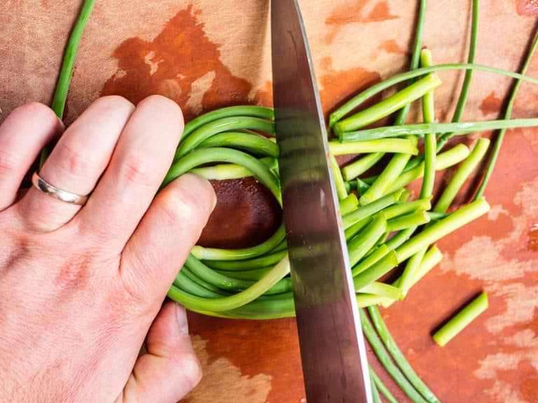 Alex's hand holding down garlic scapes to cut with a knife