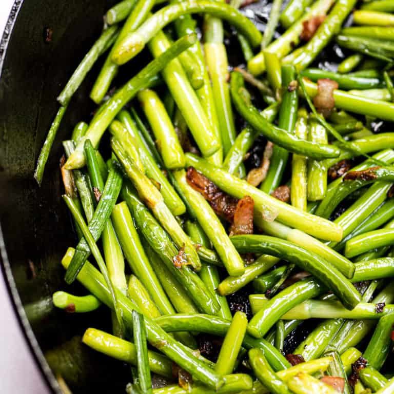 Cooked garlic scapes with bacon in a frying pan
