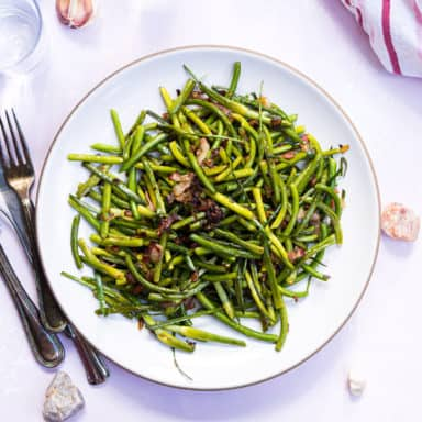 A plate of sautéed garlic scapes with bacon on a white plate