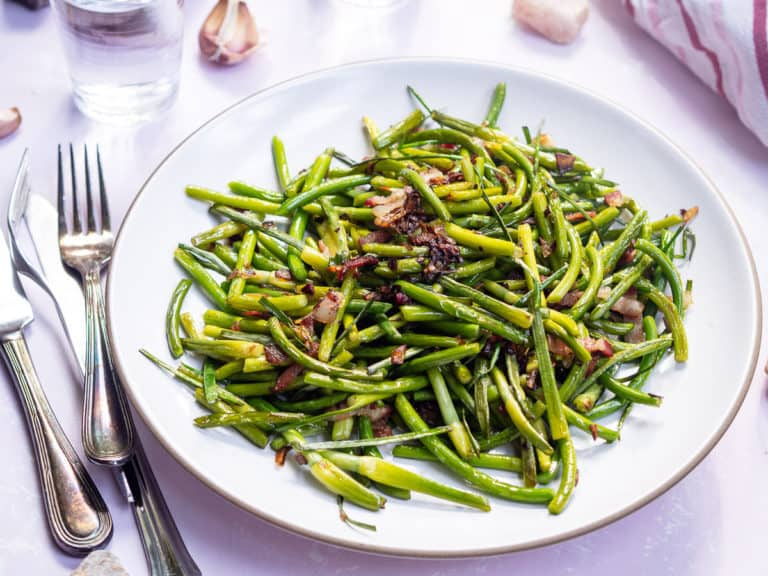 A plate of sautéed garlic scapes with bacon on a white plate next to forks and a napkin