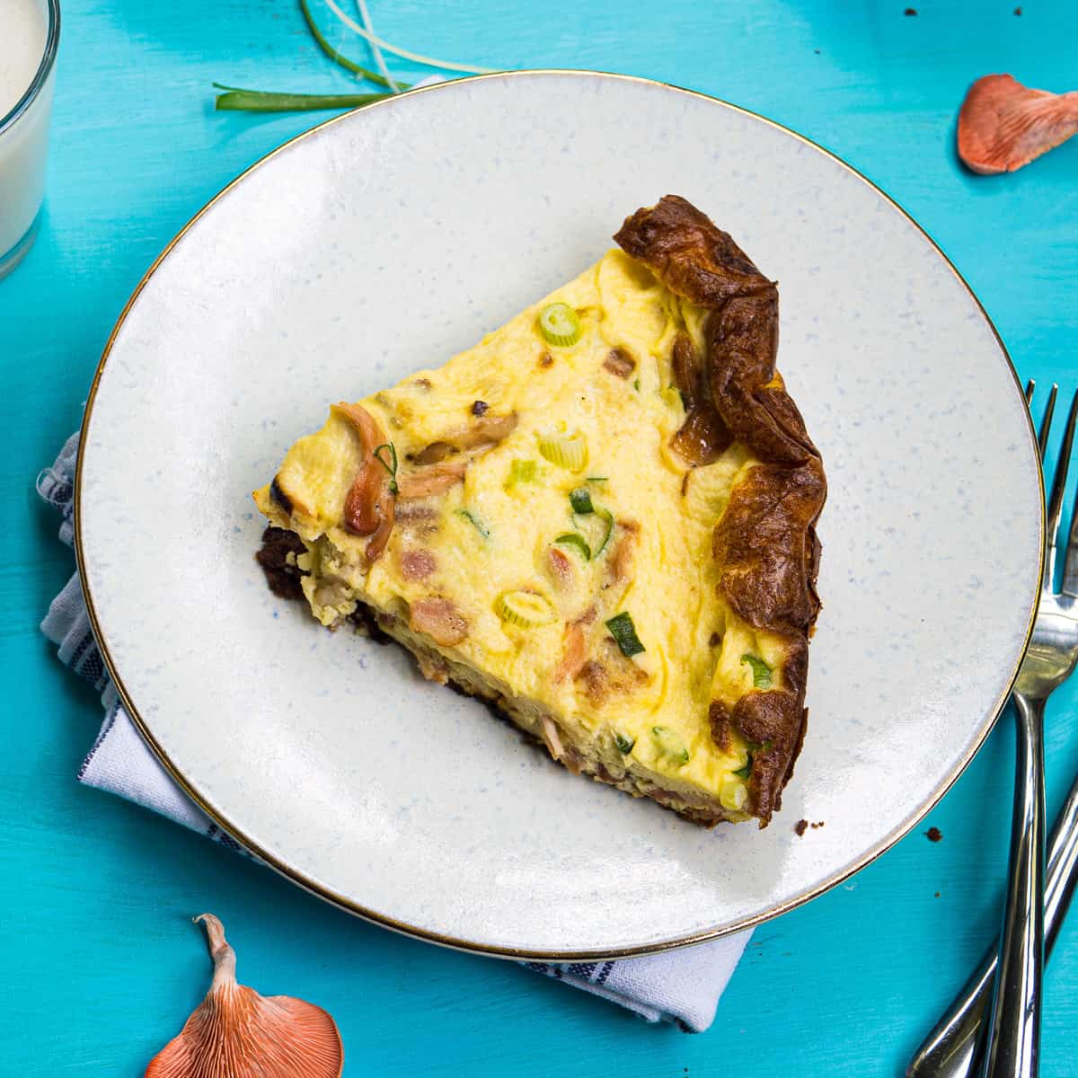 A slice of pink oyster mushroom quiche on a white plate
