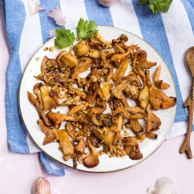 Sautéed garlic butter pink oyster mushrooms on a white plate with a cilantro garnish