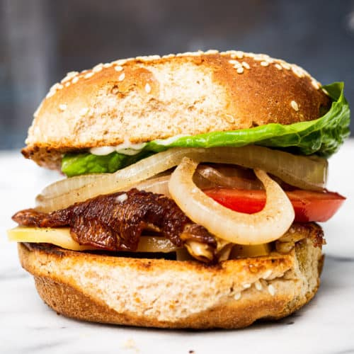 A meatless mushroom burger with lettuce, onion, and tomatoes on a marble surface