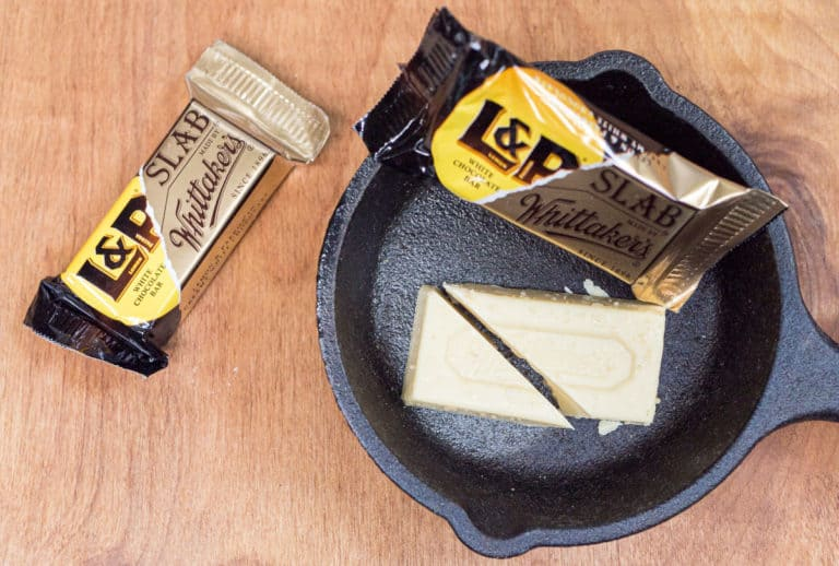 A bar of Whittaker's chocolate flavored with Lemon and Paeroa on a cast-iron skillet