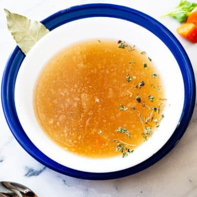 A bowl of chicken broth in a white bowl on a blue plate