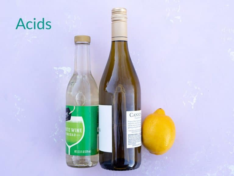 A bottle of white wine vinegar, white wine, and a lemon