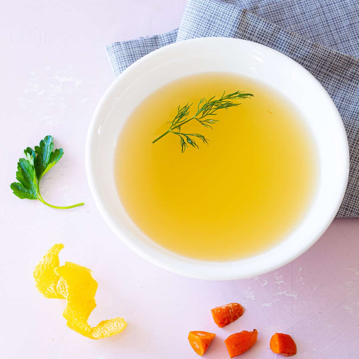 A bowl of court bouillon next to a lemon peel, diced carrot, and a leaf of parsley with a napkin