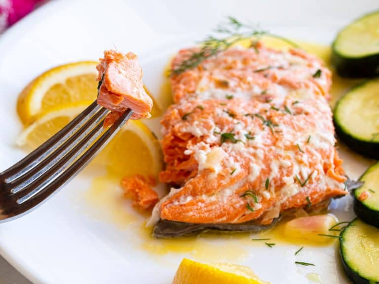 A bite of poached salmon on a fork next to a big piece of salmon