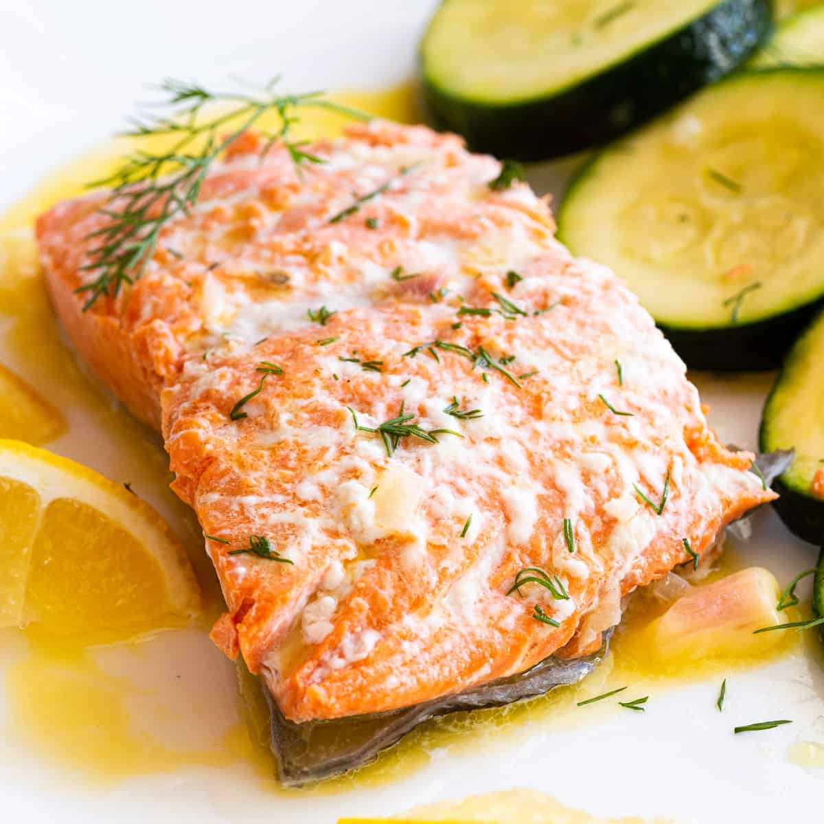 A plate of poached salmon with zucchini and a lemon wedge with a sprig of dill