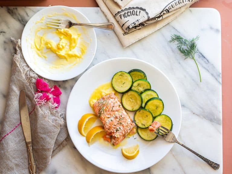 A plate of poached salmon with zucchini and lemon wedges next to a plate of beurre blanc sauce