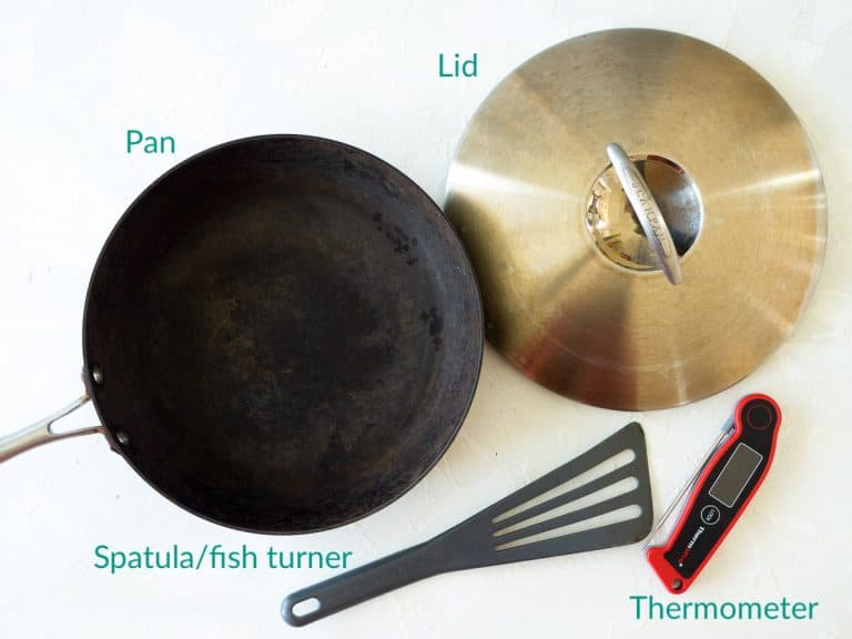 The recommended equipment for poaching salmon showing a pan and a thermometer