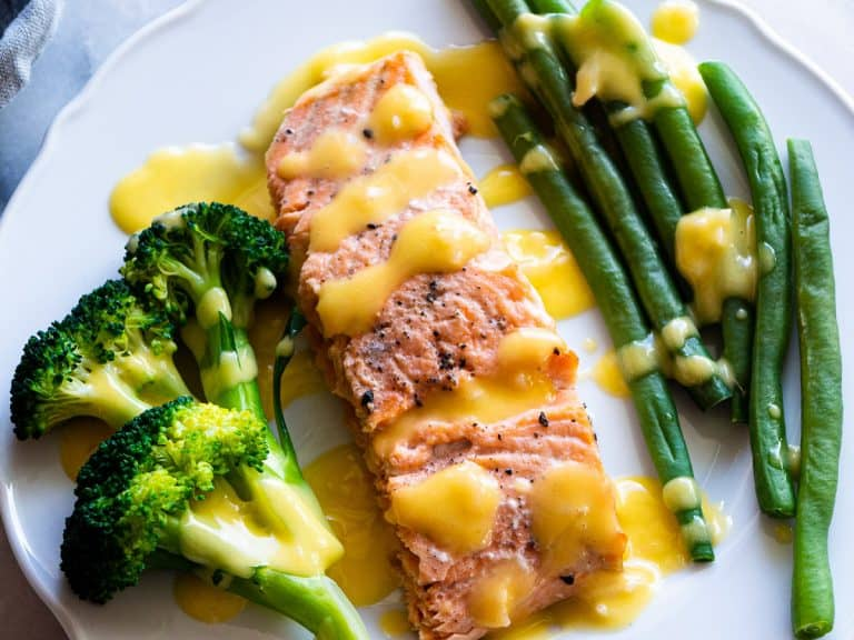 Poached salmon with broccoli and green beans slathered in beurre blanc sauce