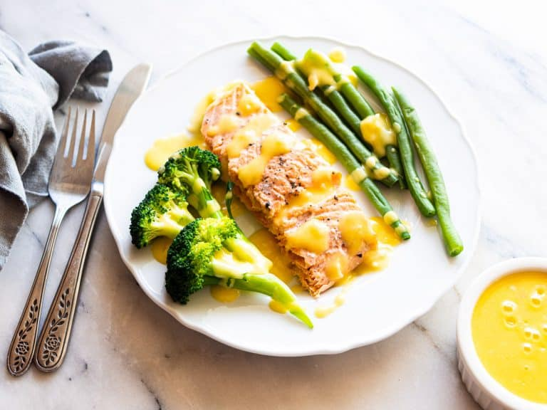 A plate of broiled salmon with broccoli and green beans slathered in beurre blanc sauce