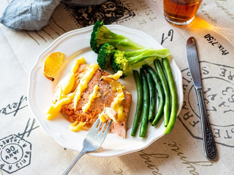 Broiled salmon with beurre blanc sauce next to broccoli and green beans on a white plate