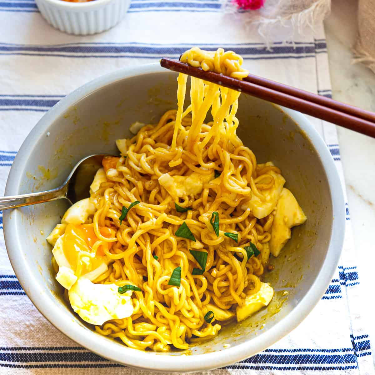 A bowl of Indomie mi goreng with eggs in grey bowl