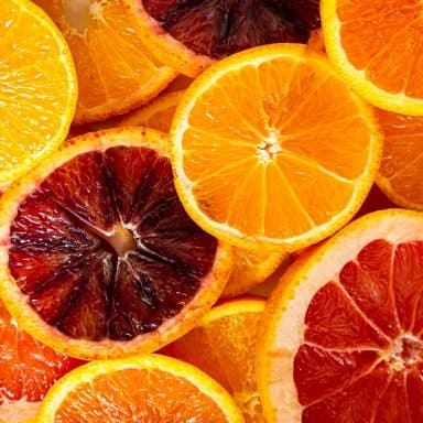 Different types of orange slices cut open layered on top of each other