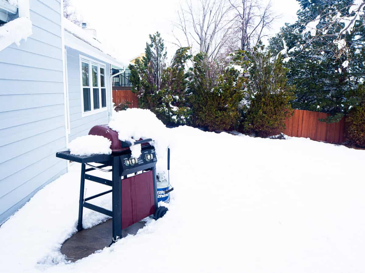 An outdoor grill packed with snow