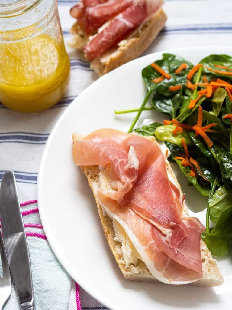 A prosciutto and brie baguette sandwich next to a green salad