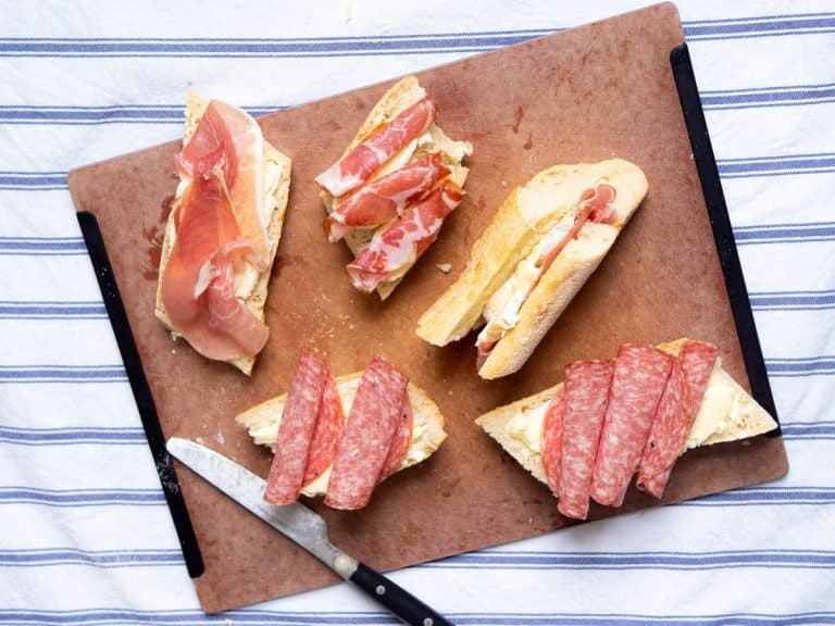 5 prosciutto and brie baguette sandwiches on a chopping board