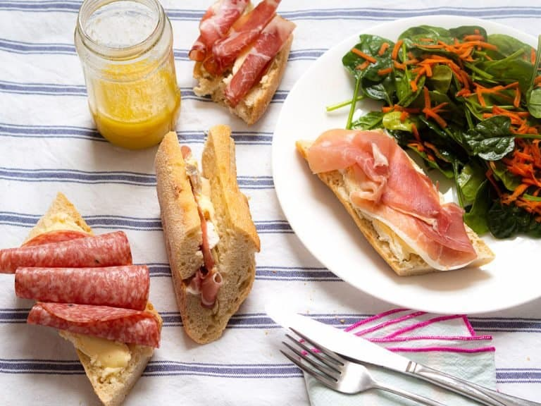 4 prosciutto and brie baguette sandwiches next to a green salad