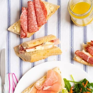 3 prosciutto and brie baguette sandwiches next to a green salad and salad dressing