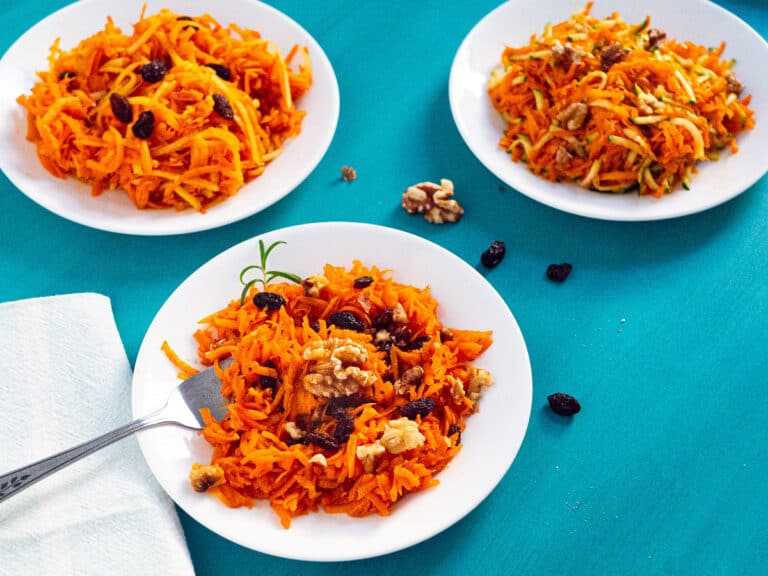 3 plates of grated carrot salad with different mix-ins next to a fork and napkin