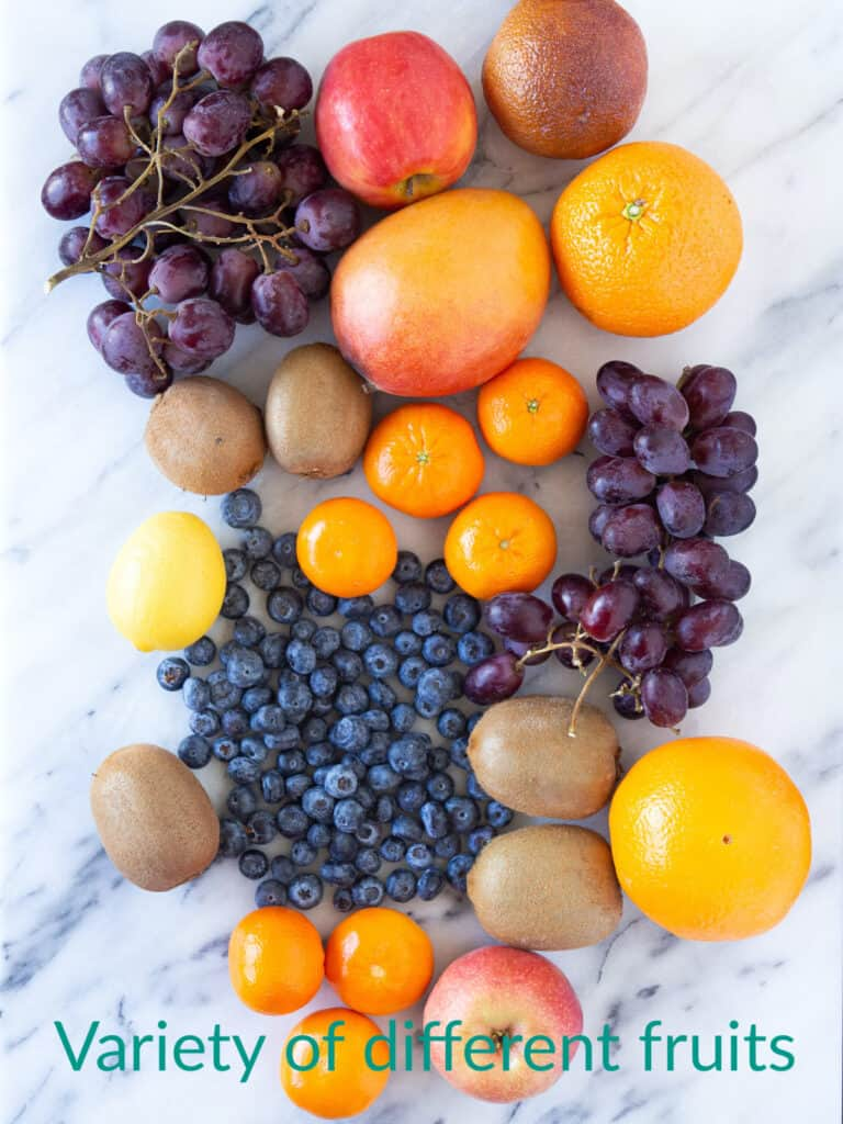 A range of fruits, including oranges, apples, grapes, blueberries, and mangoes