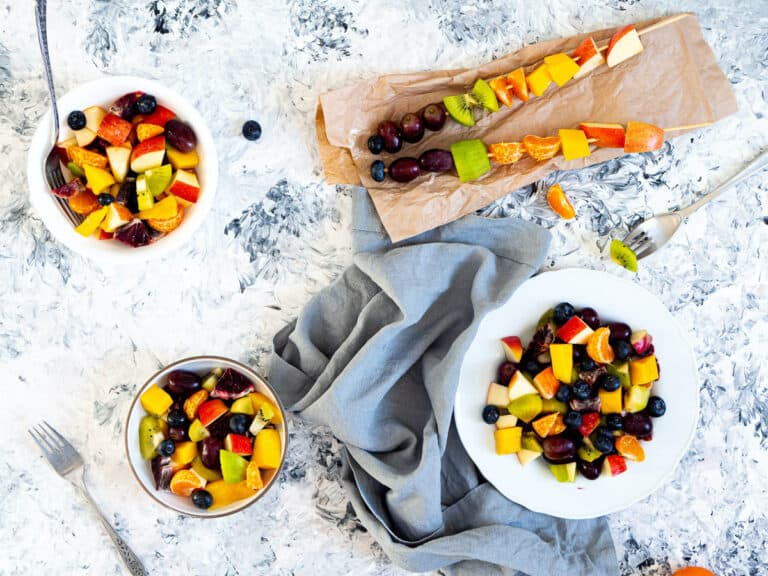3 bowls of fruit salad next to 2 fruit kebabs