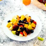 A plate of fruit salad next to a mandarin and a bunch of grapes
