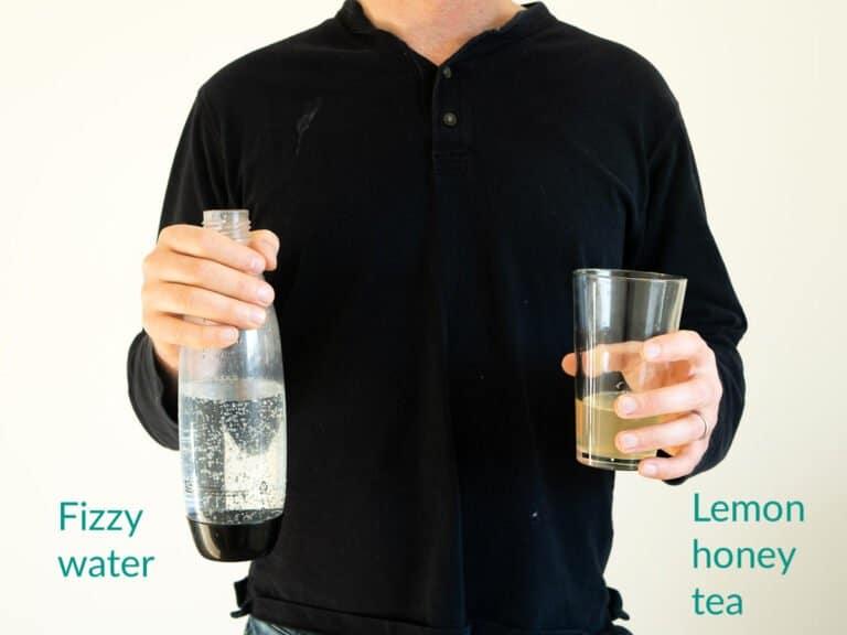 Alex holding a bottle of fizzy water next to lemon honey tea