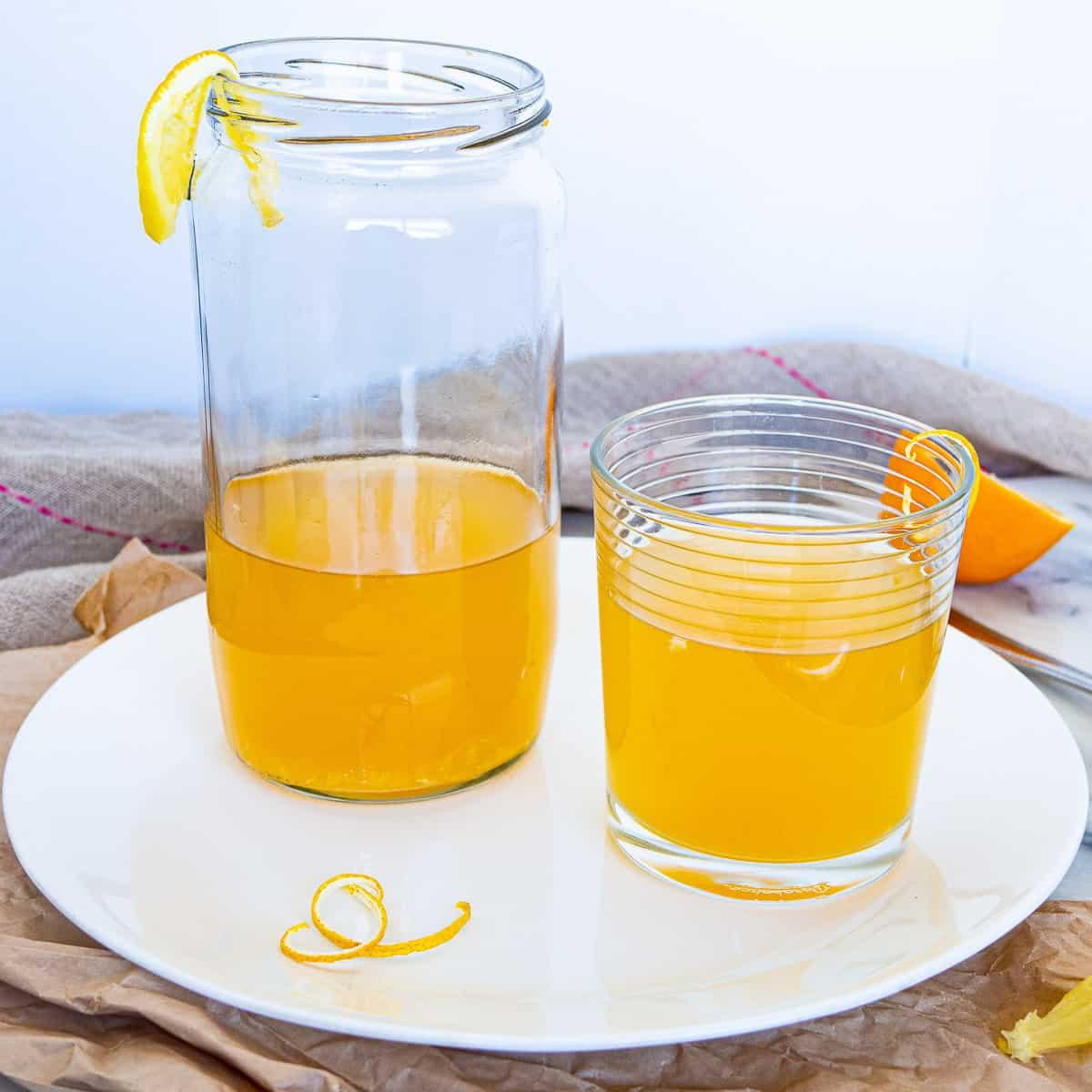 2 glasses of lemon honey tea on a white plate with lemon peel garnishes