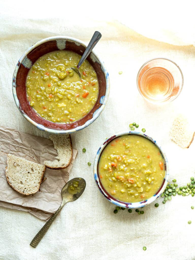 2 bowls of split pea soup next to bread and spoons