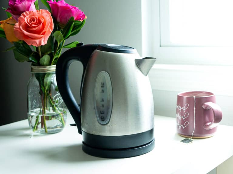 An electric kettle next to a mug of hot tea and a bouquet of roses