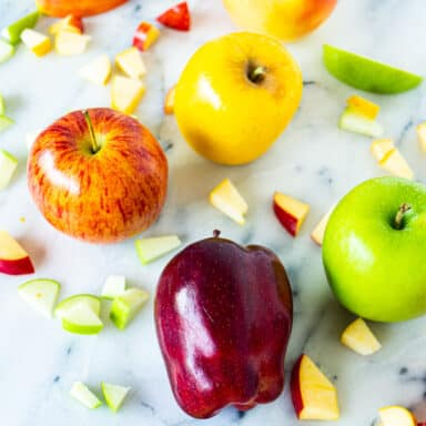 4 different colored apples with apple slices