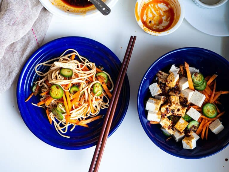 2 plates full of spicy tofu noodle salad with carrot and cucumber