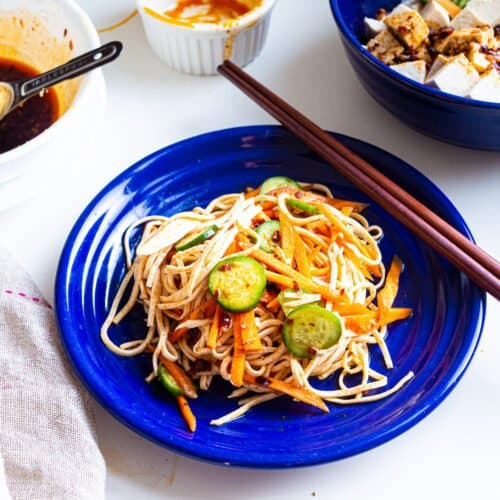Spicy tofu noodle salad with carrot and cucumber on a blue plate