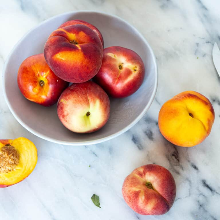 A bowl of different peaches and nectarines