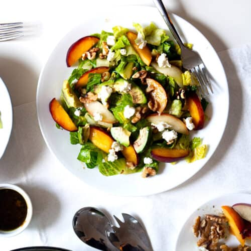 A plate of summer salad with peaches next to balsamic vinegar and lemon salad dressing