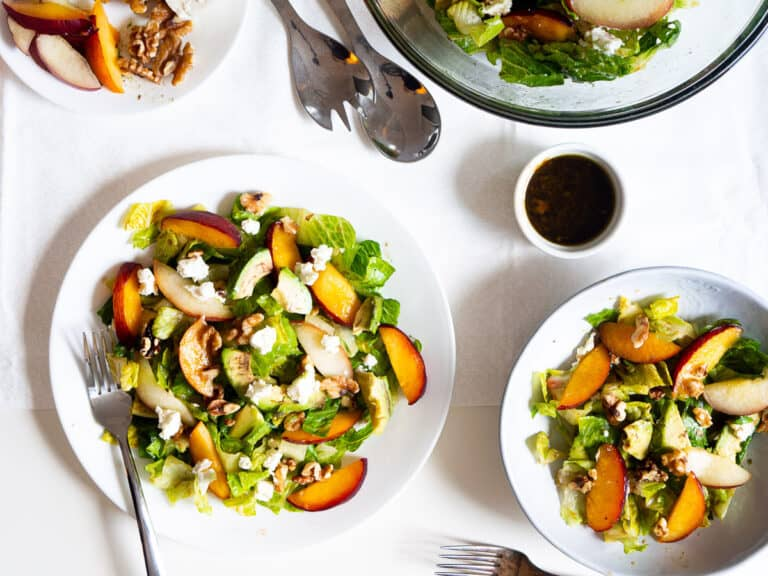 2 plates of summer salad with peaches, romaine lettuce, walnuts, avocados, and goat cheese