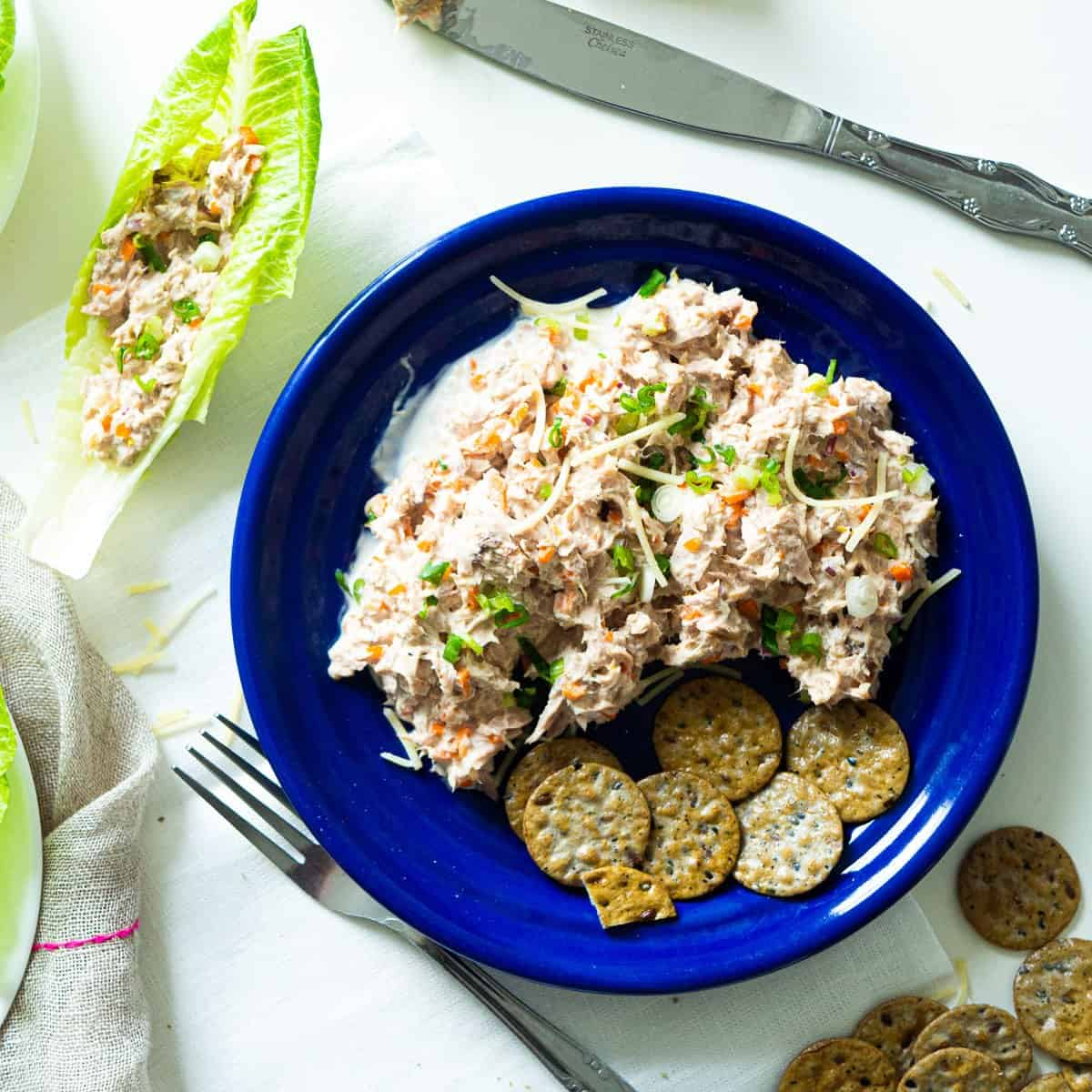 A plate of tuna salad next to lettuce cups with tuna salad inside