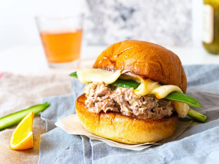 A tuna melt sandwich next to a wedge of lemon