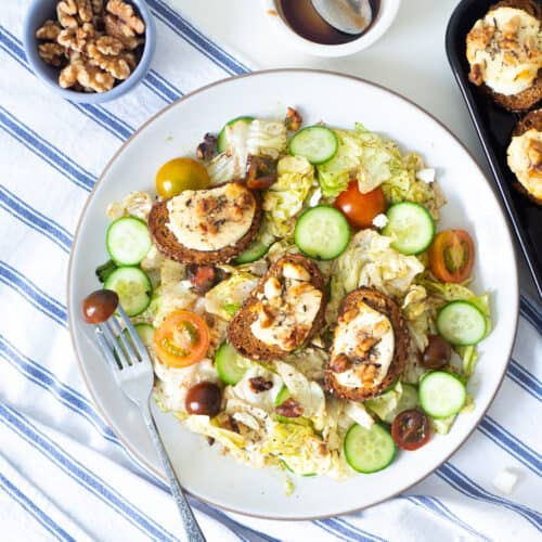 A plate of salade de chèvre chaud (warm French salad with toasted goat cheese) next to walnuts
