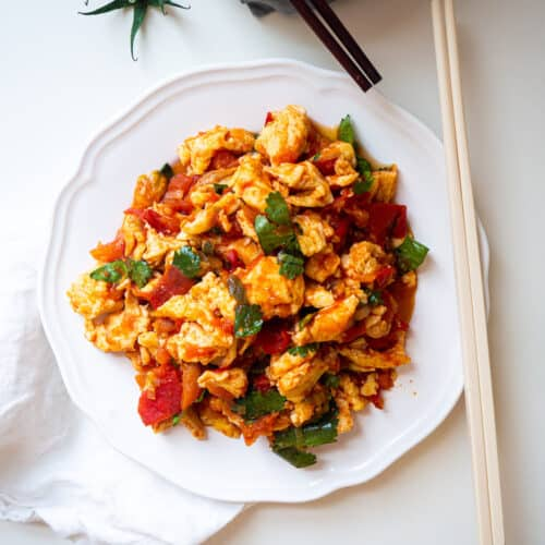 Chinese egg and tomato stir fry with cilantro on a white plate next to a pair of chopsticks