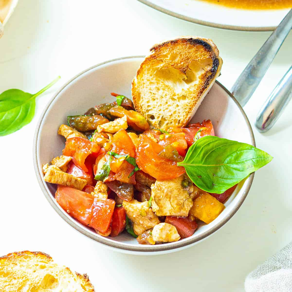 A bowl of marinated and chopped caprese salad with toasted bread