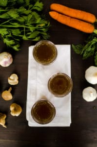 Beef Broth in 3 little mason jars on a white napkin with mushrooms on the left and garlic on the right.